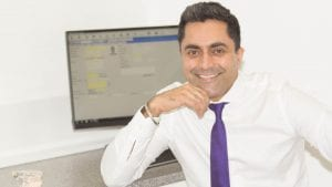 Wolverhampton Braces Dentist Dr Dave Dehal smiling in dental surgery with orthodontic model