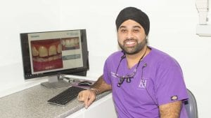 Dr Gurpreet Nandra smiling and sitting at surgery computer at Wolverhampton Dentist
