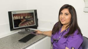 Wolverhampton Dentist Dr Kiran Mandair sitting by computer with picture of teeth